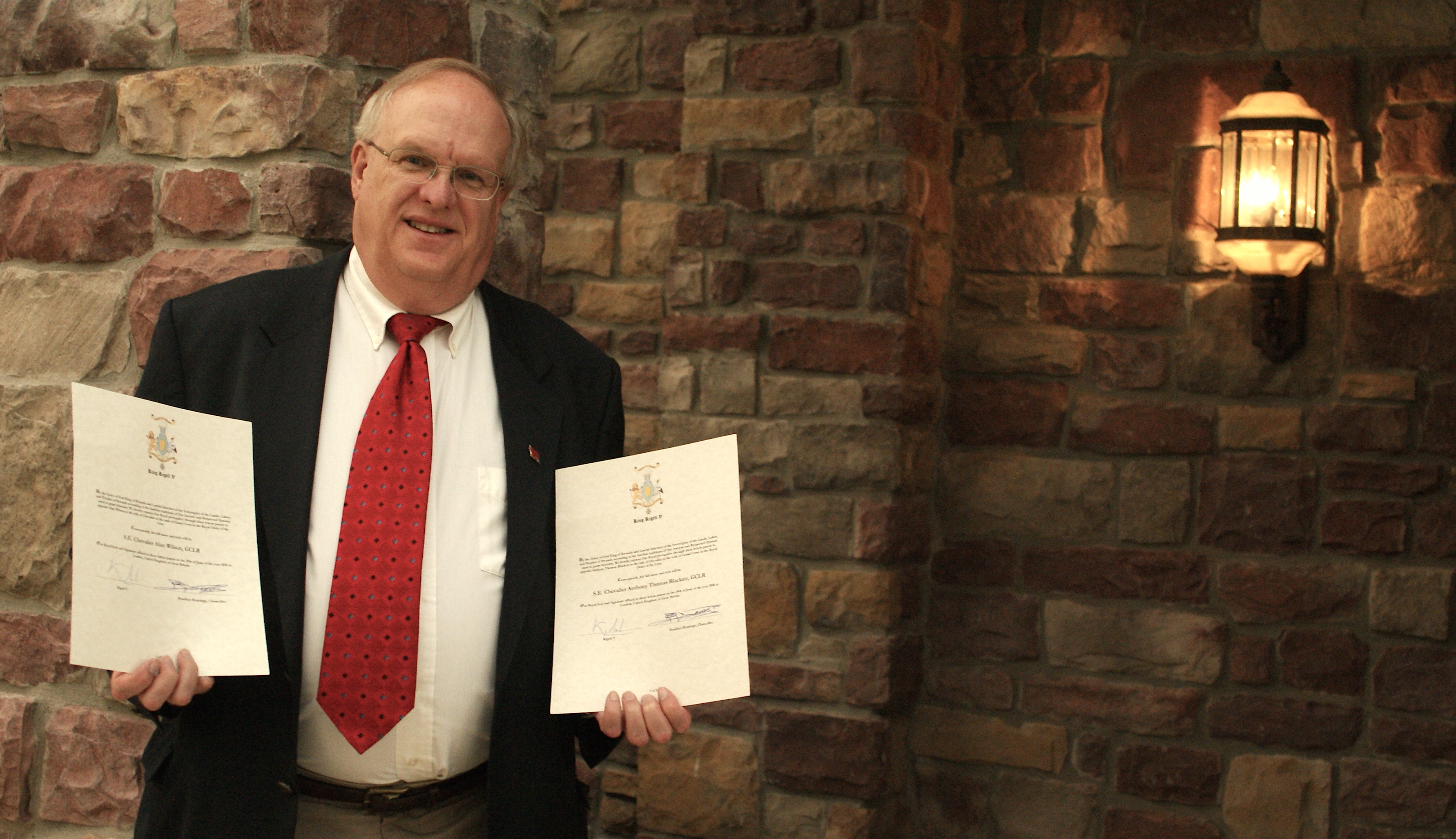George Horwatt, President of The Welsh Cultural Endeavor of Northeastern Pennsylvania, holds proclamations signed by King Kigeli V of Rwanda to knight Welsh Researchers Alan Wilson and Baram Blackett.